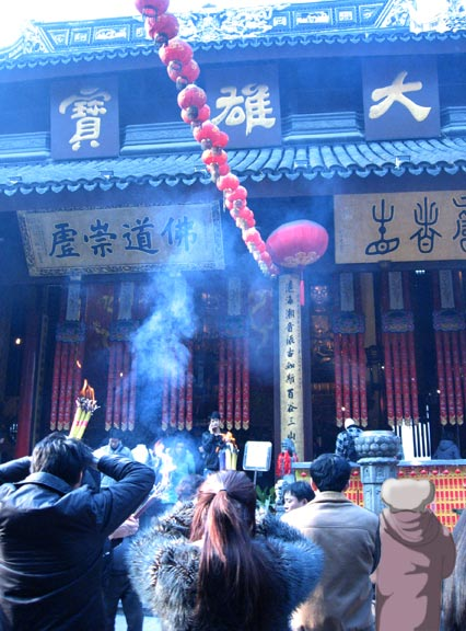 Chinese pray with burning joss sticks.